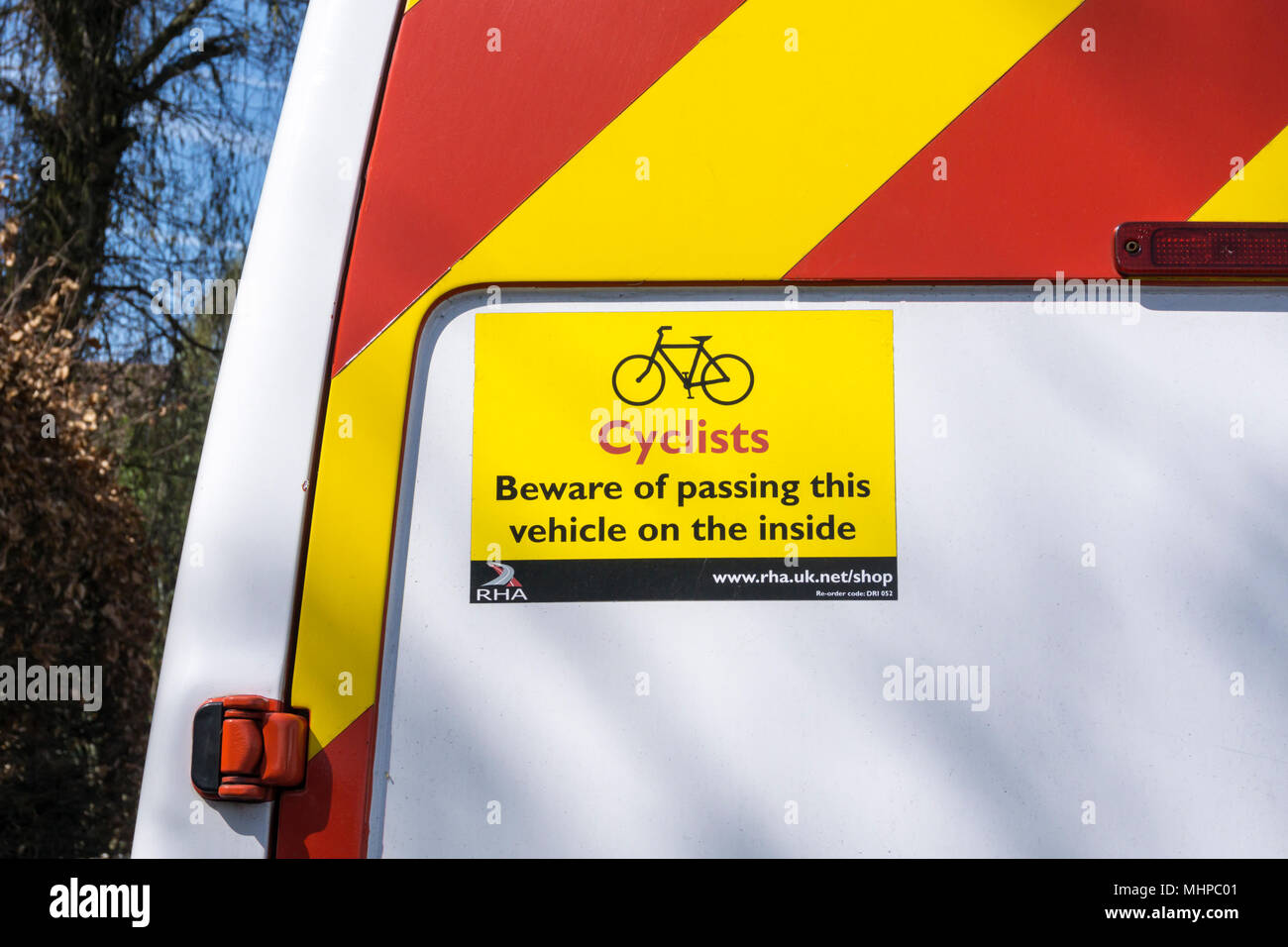Sign on back of van reads:  Cyclists Beware of passing this vehicle on the inside. - Stock Image