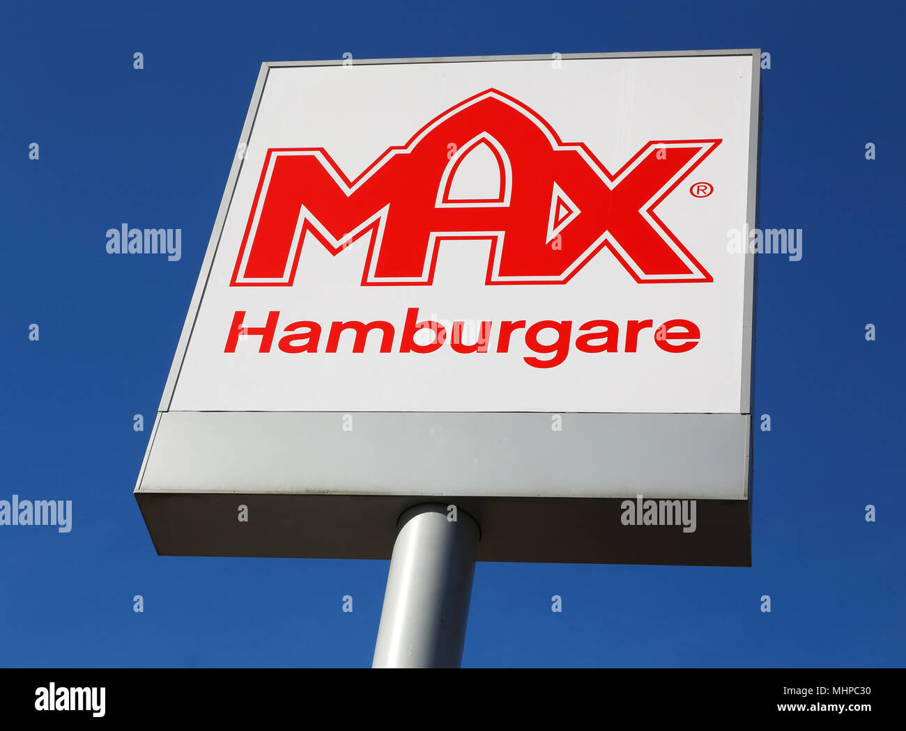 Ornskoldsvik, Sweden - March 28, 2014: The Swedish hamburger chain Max logo on pole against blue sky. - Stock Image