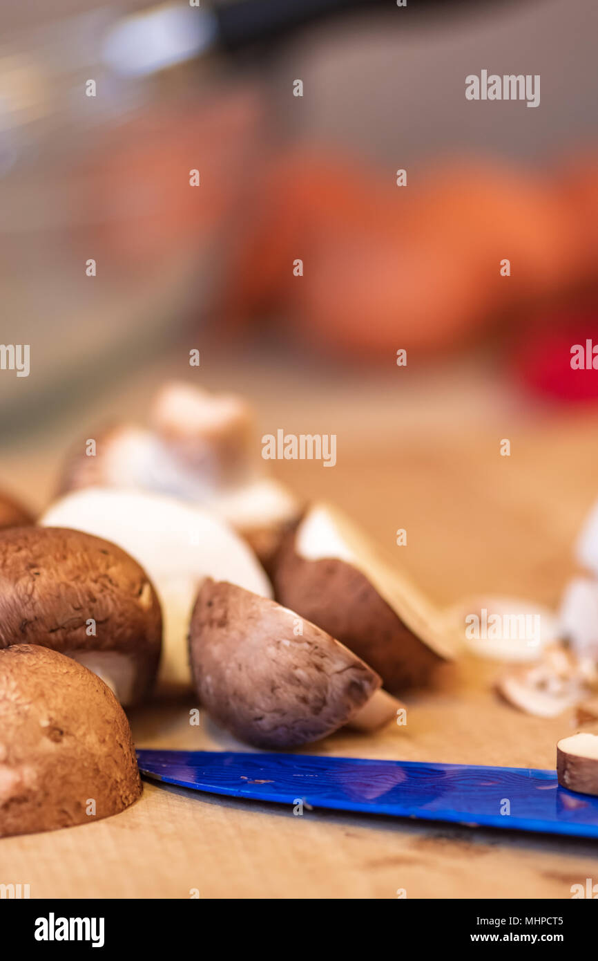 Sliced mushrooms on wood cutting board, blue knife blade. - Stock Image