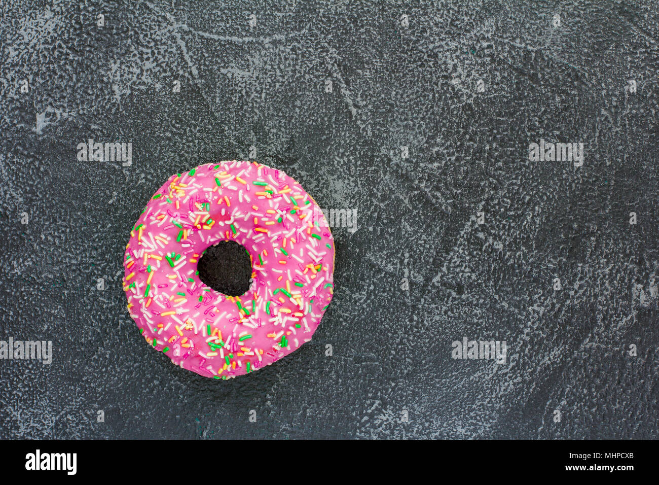 A single donut on dark stone background - Stock Image