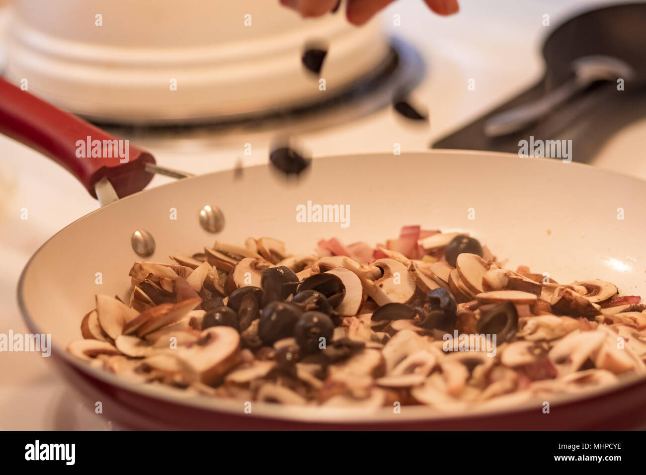 Hand dropping black olives in to frying pan. Chopped black olives, sliced mushrooms and red onion in red and white frying pan. - Stock Image