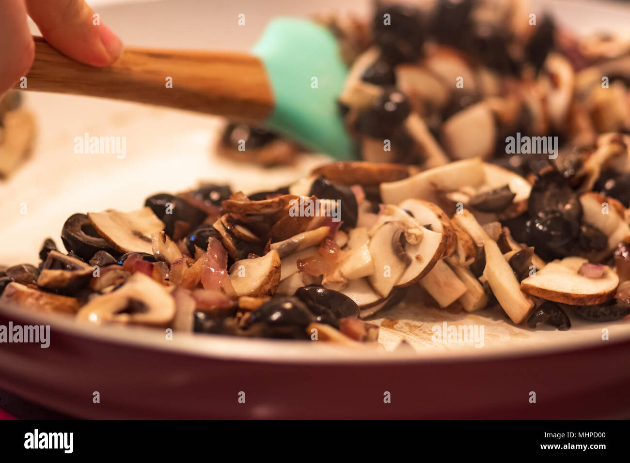 Hand using spatula to stir chopped black olives, red onions and sliced mushrooms in a frying pan. - Stock Image