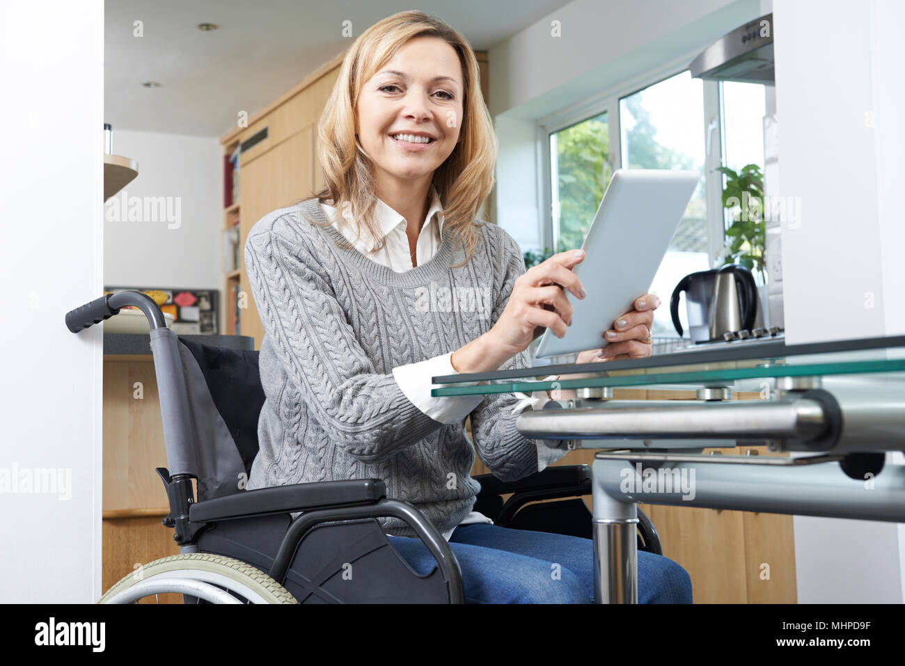 Disabled Woman In Wheelchair Using Digital Tablet At Home - Stock Image
