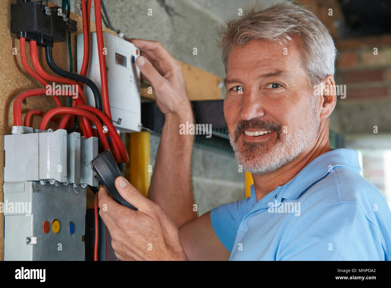 Portrait Of Man Taking Reading From Electricity Meter - Stock Image