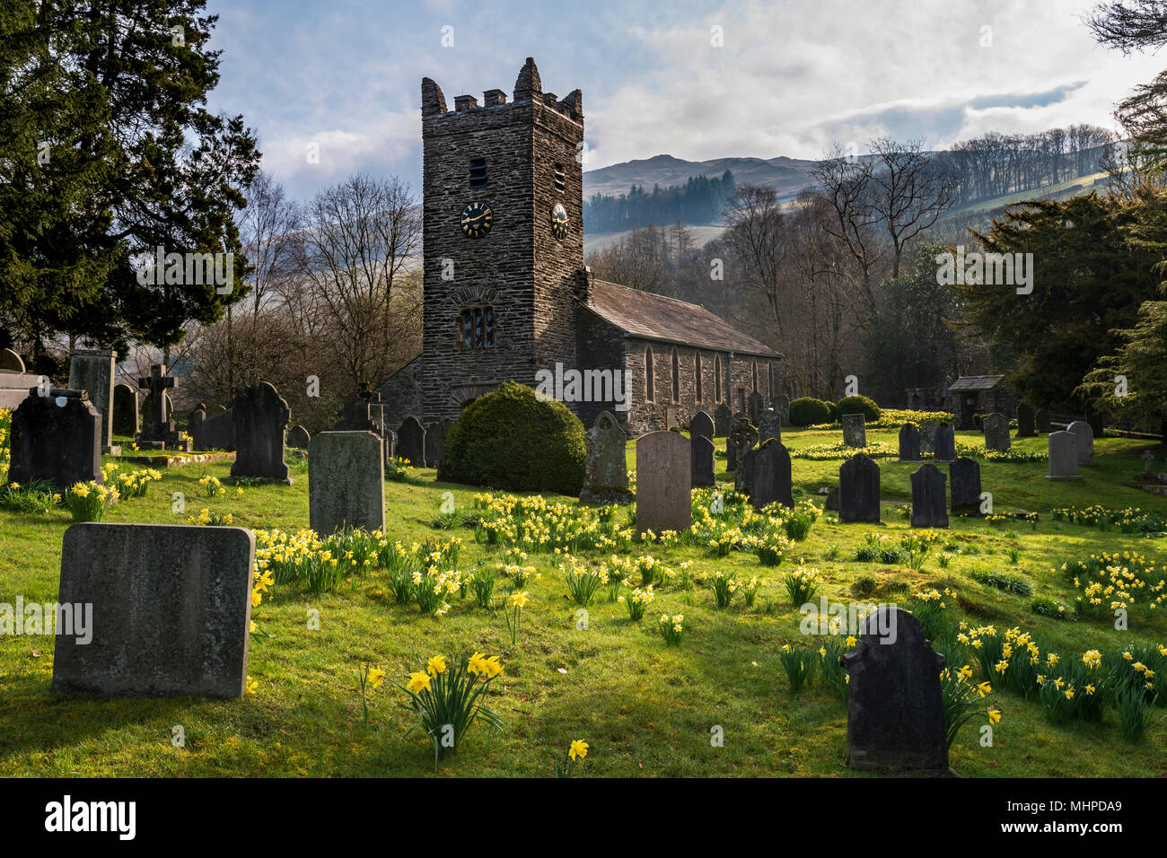 Troutbeck church surrounded by Daffodils and mist covered fells - Stock Image