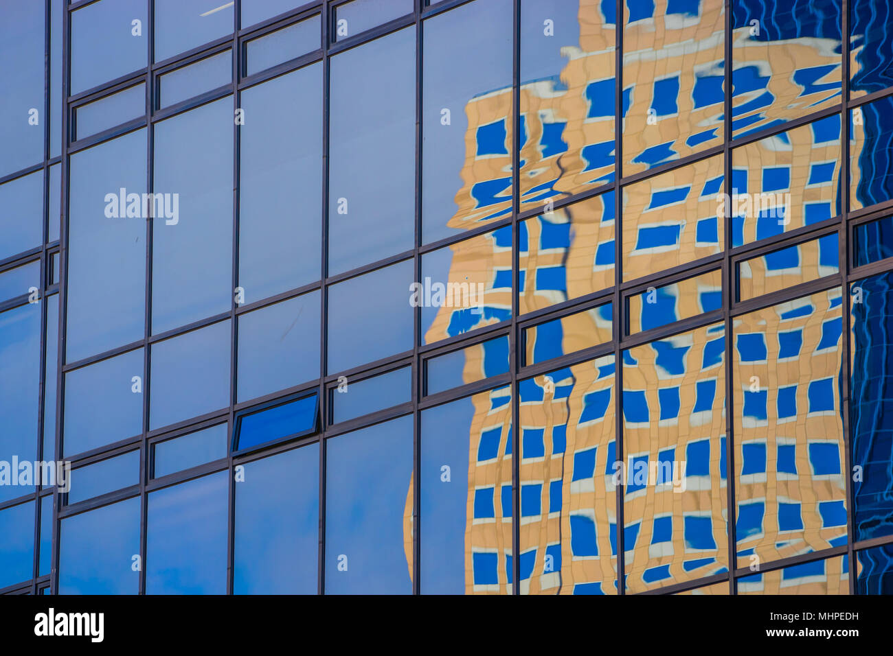 Warped view of reflected building seen in the glass and metal of opposing skyscraper. - Stock Image