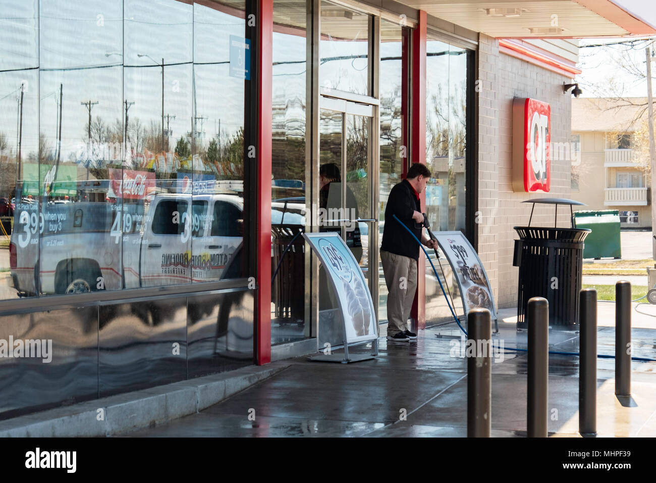 A young Caucasian man employee power washes the cement outside of a QuickTrip store in Wichita, Kansas, USA. - Stock Image
