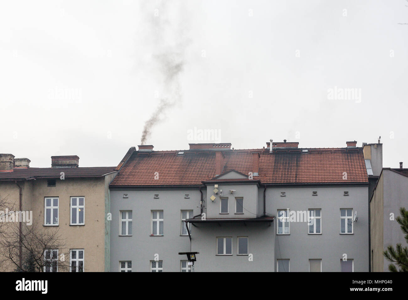 Oswiecim, Poland - Black smoke coming out of the tenement house`s chimney while coal-loving Poland struggles with killer smog. Air pollution. - Stock Image