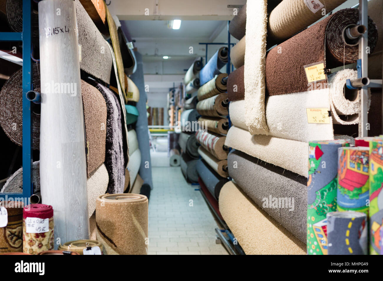 Carpet rolls on a rack in a warehouse - Stock Image