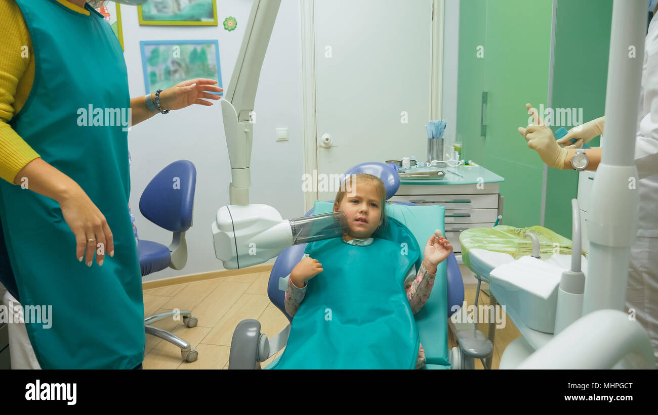 Child with a mother at a dentist's reception. The girl lies in the chair, behind her mother. The doctor works with an assistant. Procedure for drilling a tooth. Setting a temporary seal. - Stock Image
