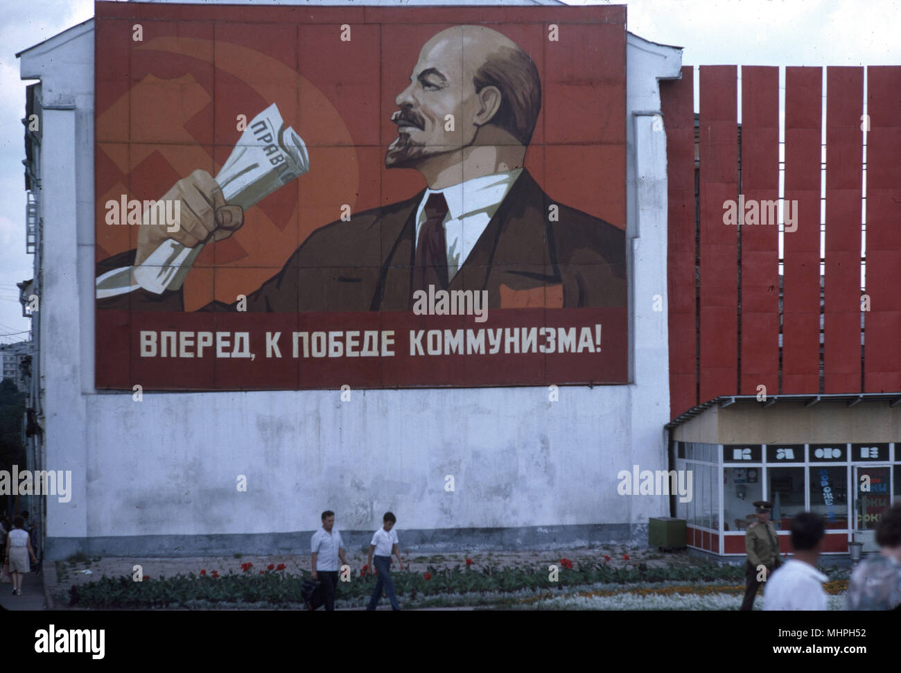 Communist poster on a wall in Vladimir, USSR -- with a profile of Lenin holding a copy of Pravda in his hand, the motto reads: Forward to the Victory of Communism!      Date: circa 1960s - Stock Image