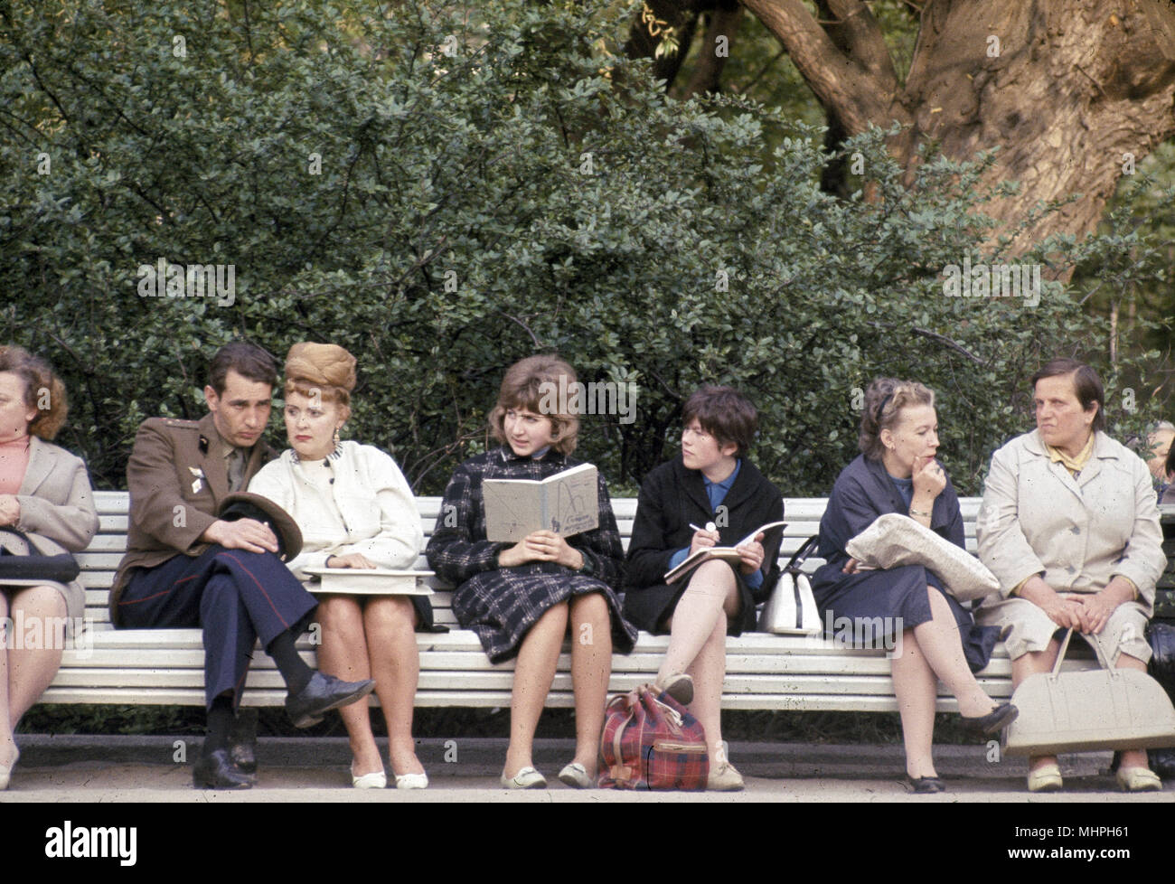 People sitting on a park bench, Leningrad (St Petersburg), USSR.      Date: circa 1960s - Stock Image