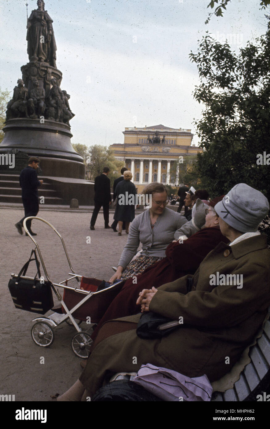 People sitting on a bench, Leningrad (St Petersburg), USSR, with a statue of Catherine the Great on the left and the Alexandrinsky Theatre in the background.       Date: circa 1960s Stock Photo