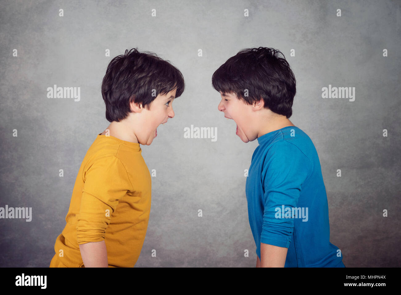 Angry children shouting over on gray background Angry children shouting over on gray background - Stock Image