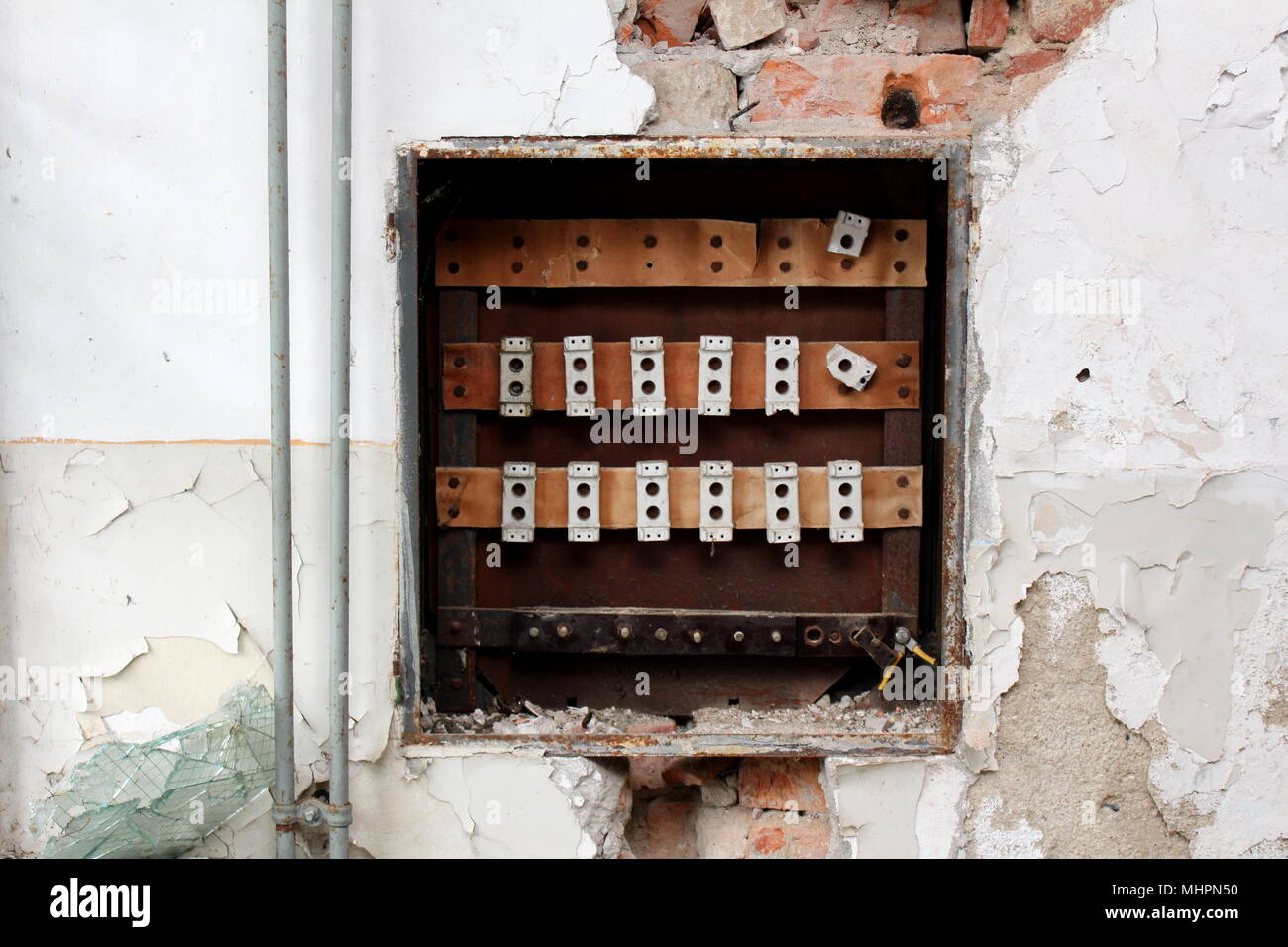 Destroyed rusted old fuse box surrounded with crumbling wall, visible  bricks, radiator pipes and