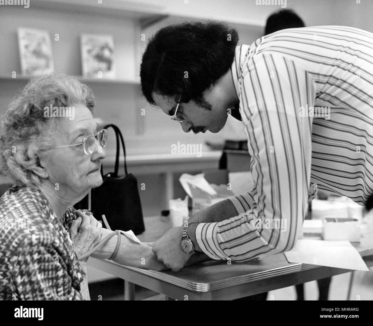 Public health worker taking a blood sample from an older woman, 1976. Image courtesy Centers for Disease Control (CDC). () - Stock Image