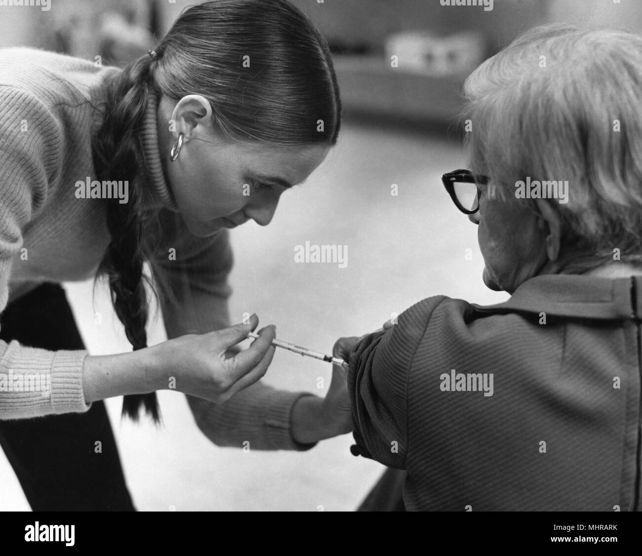 Public health worker vaccinating an older woman, with a syringe, 1976. Image courtesy Centers for Disease Control (CDC). () - Stock Image