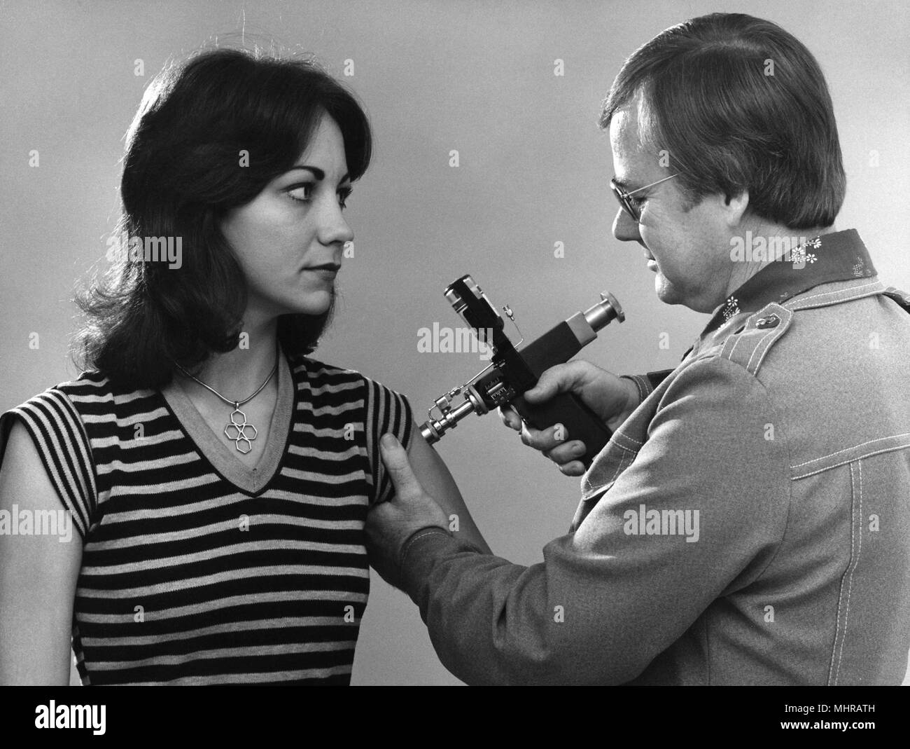Public health worker vaccinating a young woman, with a jet injector, 1976. Image courtesy Centers for Disease Control (CDC). () - Stock Image