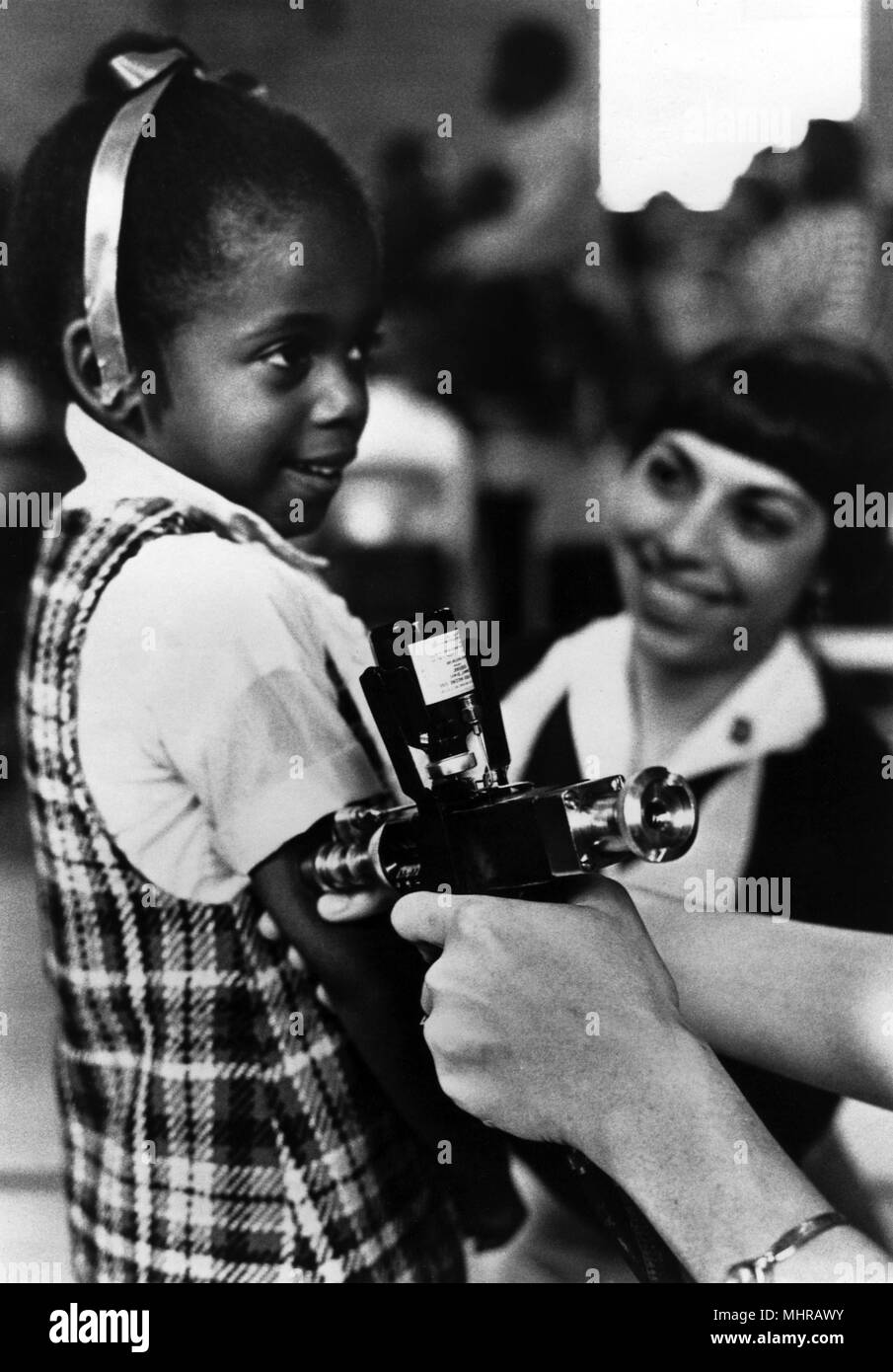 Public health worker vaccinating a young girl, with a jet injector, 1986. Image courtesy Centers for Disease Control (CDC). () - Stock Image
