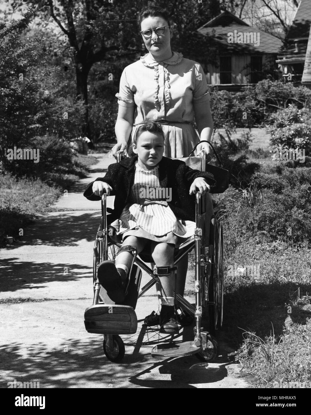 Young woman pushes a child in a wheelchair, image used to encourage individuals to receive polio vaccinations, 1968. Image courtesy Centers for Disease Control (CDC). () - Stock Image