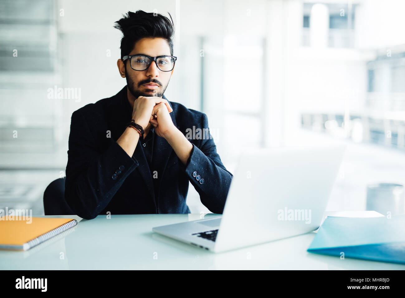 Indian business Man using laptop with hands hand on chin in his office - Stock Image