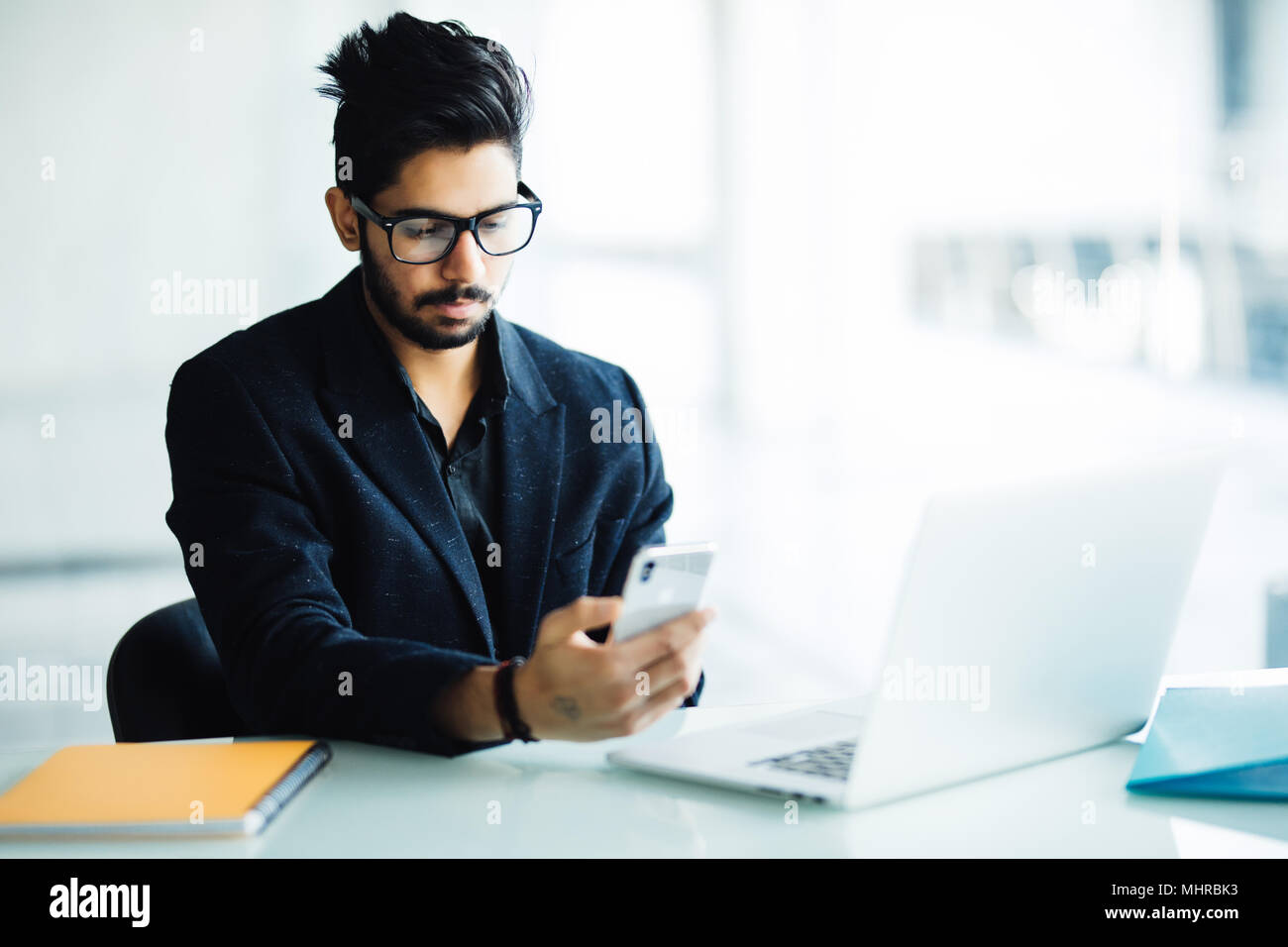 Indian CEO of company in his business office at desk, reading text on smartphone - Stock Image