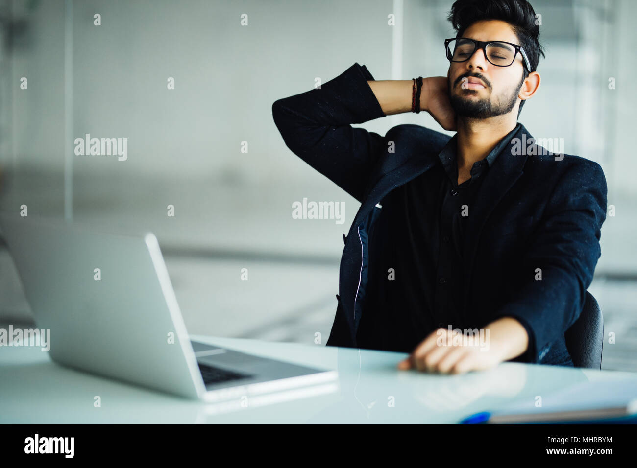 Tired and worried indian business man at workplace in office Stock Photo