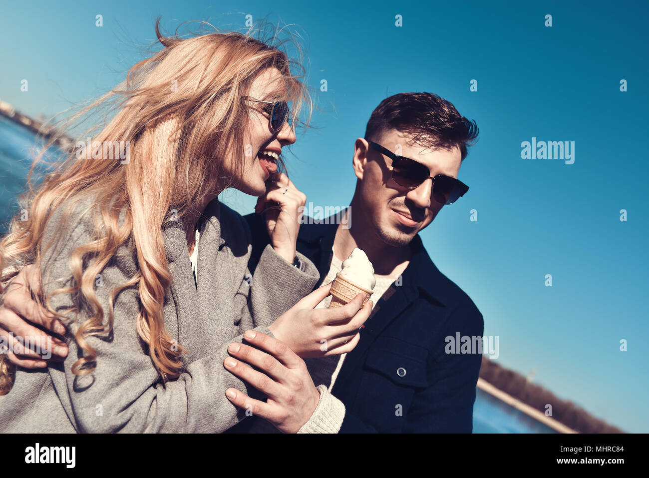 Beautiful couple stay at city embankment and eating the ice cream - Stock Image