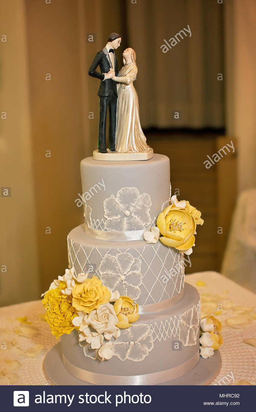 A Three Tiered Wedding Cake In Grey Yellow And White Colors Stock