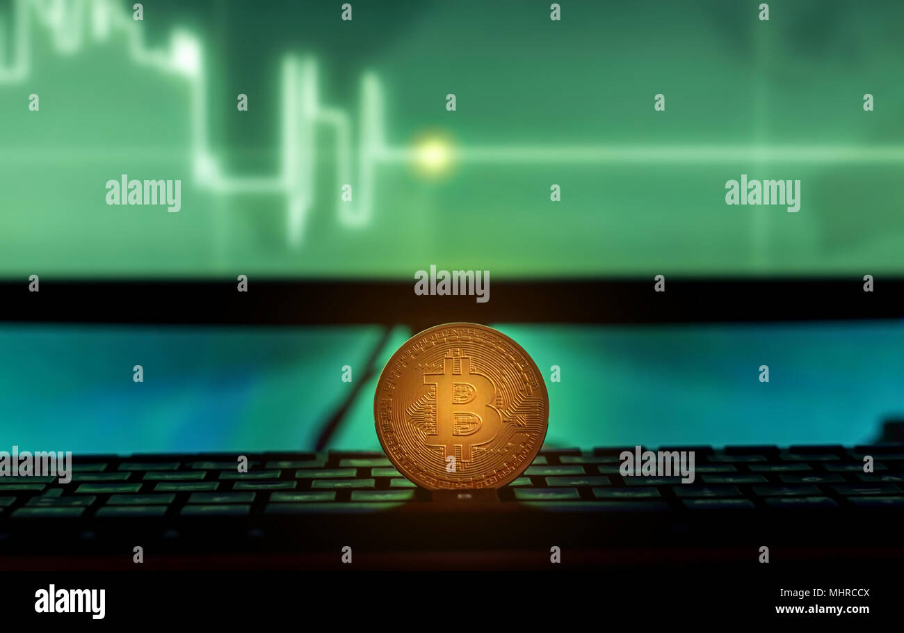Physical Bitcoin placed on Laptop computer with charts on screen, dark themed Stock Photo