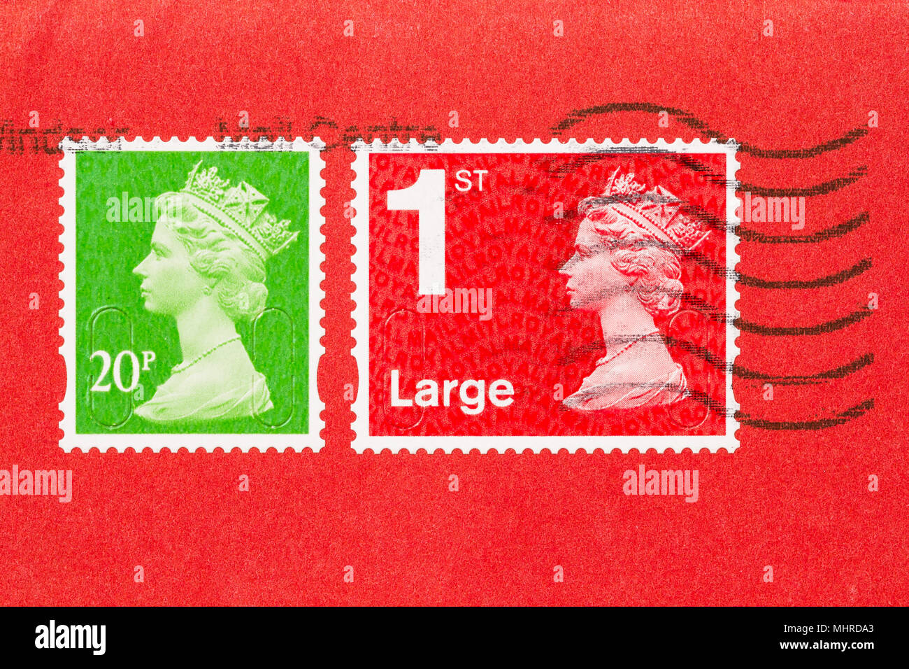 Close up of an envelope with 2 stamps, ones red, one green, of Queen Elisabeth II. UK postage stamp on red paper. - Stock Image