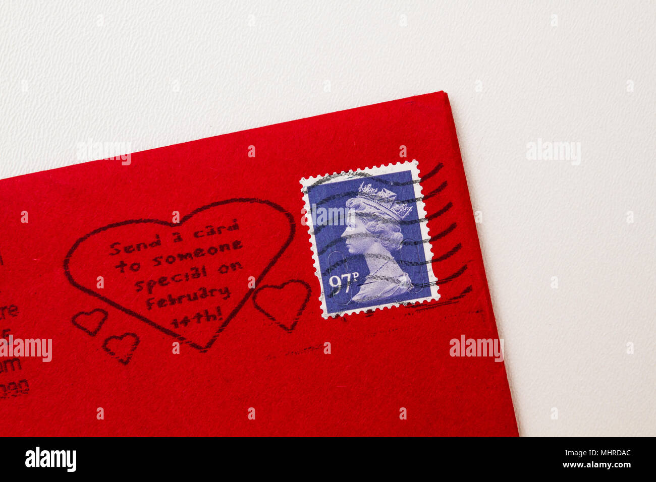 Red envelope corner with a blue stamp of Queen Elisabeth II. UK postage  with Valentine's Day dedication isolated on white background. - Stock Image
