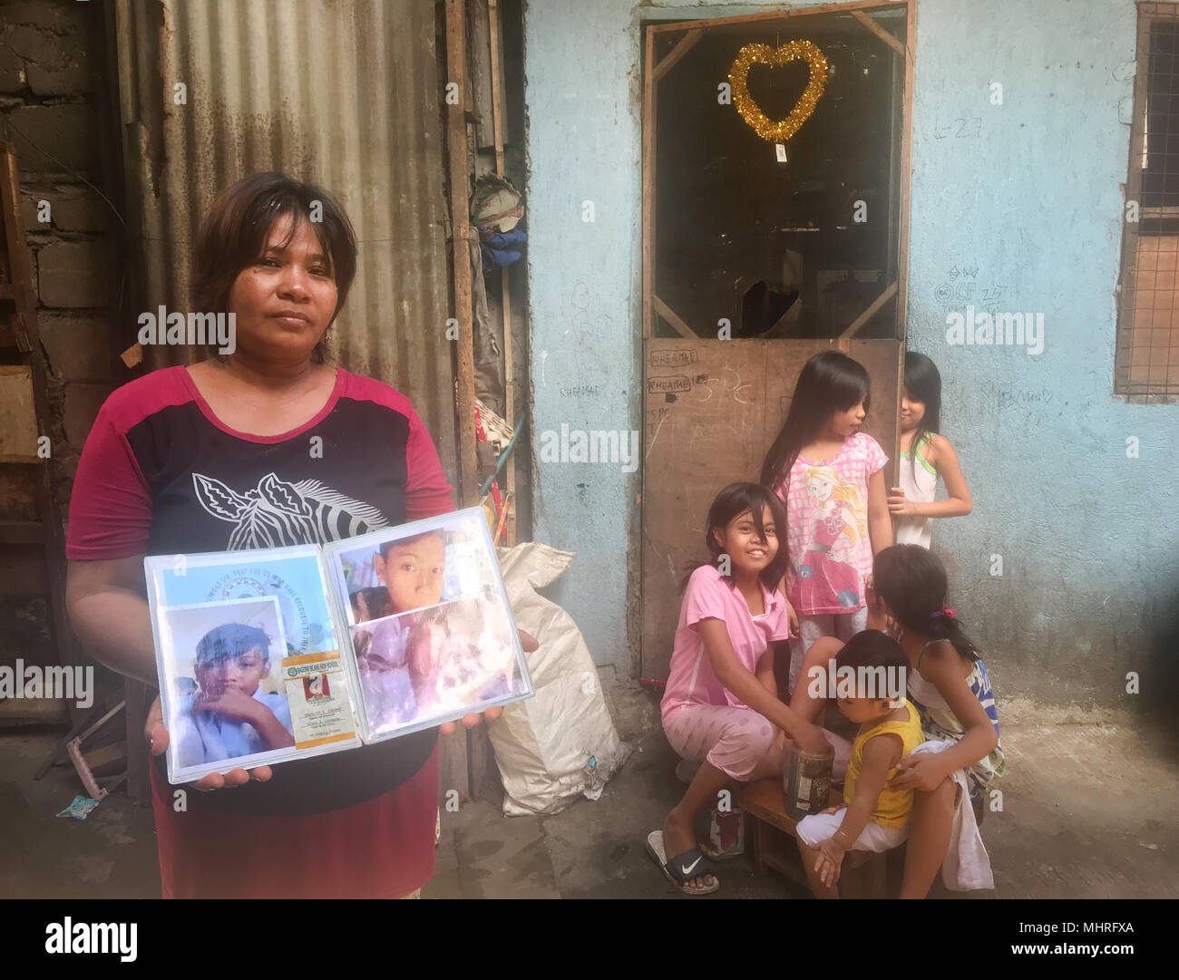 19 April 2018, Philippines, Manila: The Filipino Emily Soriano showing photos in front of her house in Bagong Silang of her son who was shot. The 15 year old is one of thousands of victims of the anti-drugs war led by president Rodrigo Duterte. Photo: Christoph Sator/dpa - Stock Image