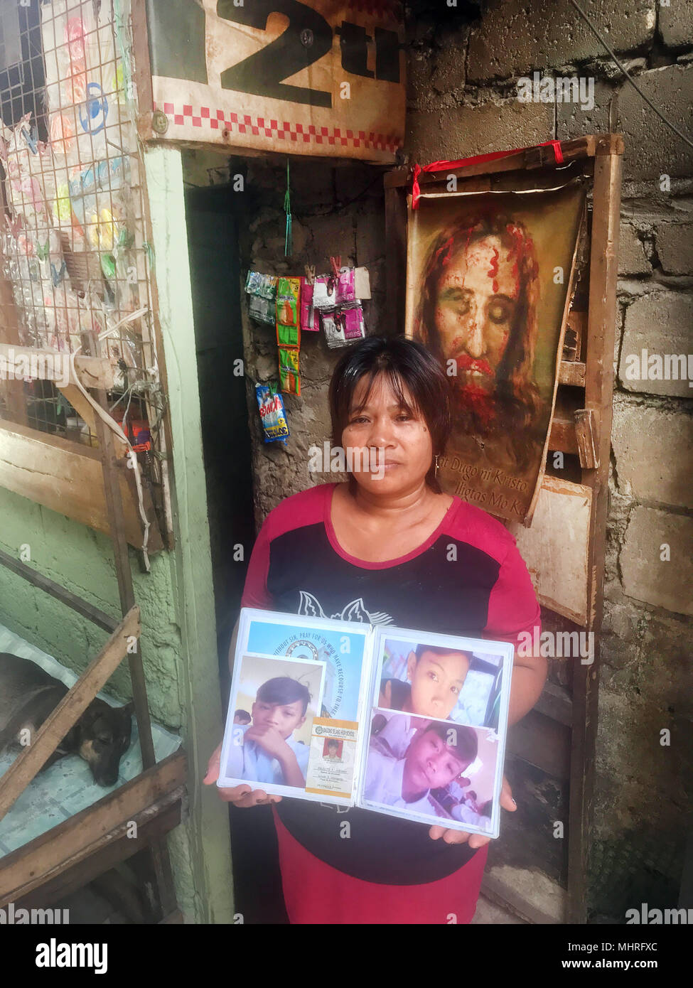 FILED - 19 April 2018, Philippines, Manila: The Filipino Emily Soriano showing photos in front of her house in Bagong Silang of her son who was shot. The 15 year old is one of thousands of victims of the anti-drugs war led by president Rodrigo Duterte. Photo: Christoph Sator/dpa - Stock Image