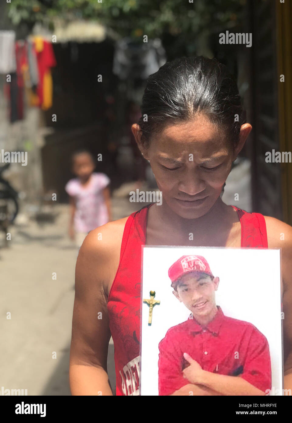 19 April 2018, Philippines, Manila: The Filipino Maria Victoria Dahohoy showing a photo of her son who was shot in Bagong Silang, a suburb of the capital Manila. The 15 year old is one of thousands of victims of the anti-drugs war led by president Rodrigo Duterte. Photo: Christoph Sator/dpa - Stock Image