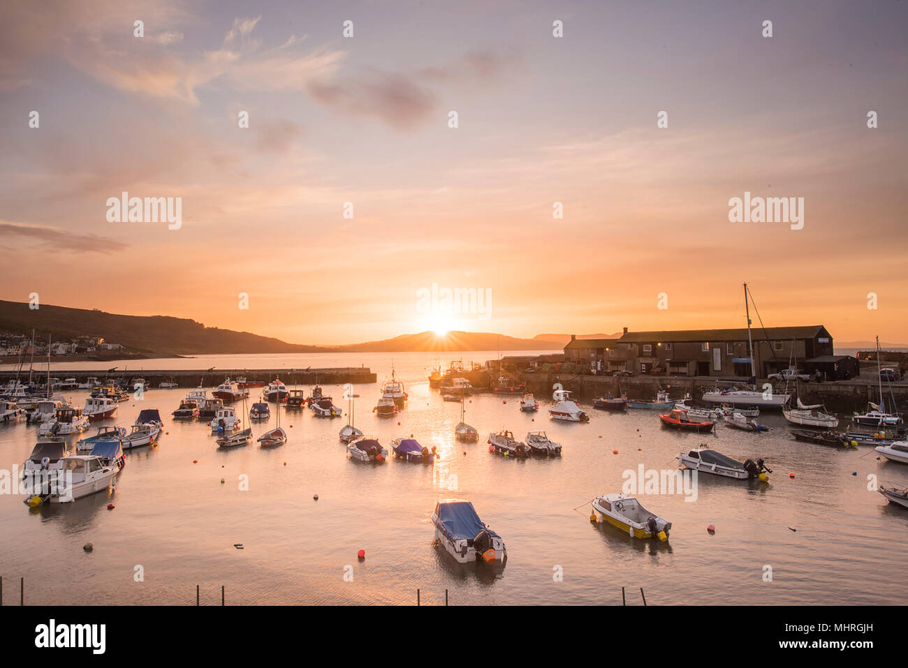 Weather, UK. 3rd May 2018. Beautiful colours over Lyme Regis Harbour, Dorset as May temperatures rise in time for the Bank Holiday weekend and the annual fossil festival. Credit: Celia McMahon/Alamy - Stock Image