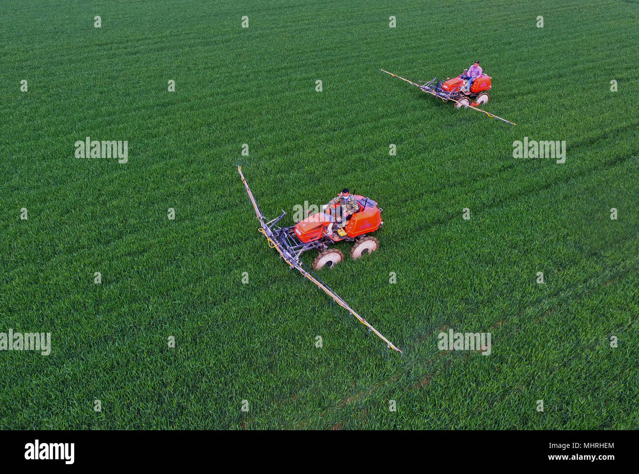 Shijiazhuang, China's Hebei Province. 2nd May, 2018. Villagers operate farm machines at a field in Nanhe County, north China's Hebei Province, May 2, 2018. Credit: Yang Shiyao/Xinhua/Alamy Live News - Stock Image