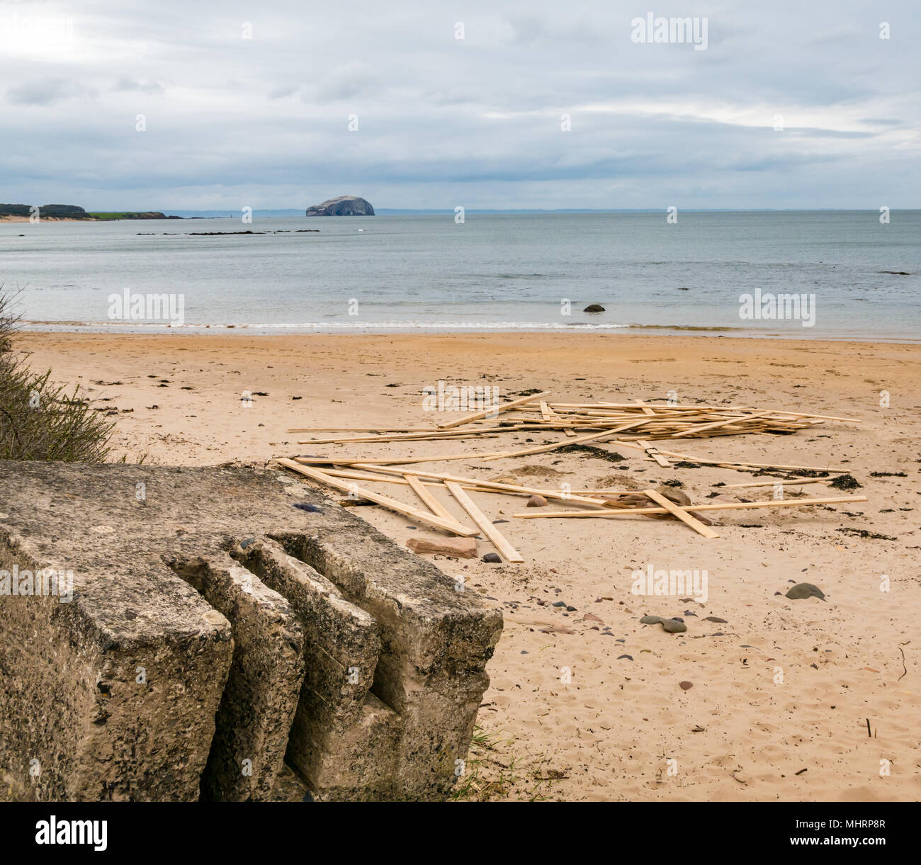 Ravensheugh Sands, East Lothian, Scotland, United Kingdom, May 2nd 2018.  A very dull grey day. Noone on the beach with a worn concrete World War II coastal defence road block, looking across the Firth of Forth towards the Bass Rock, home to the world's largest Northern gannet colony. Planks of timber still lie washed up after spilling from cargo vessel 'Frisian Lady' which lost the timber bundles during severe weather on 2nd March during the 'Beast from the East' - Stock Image