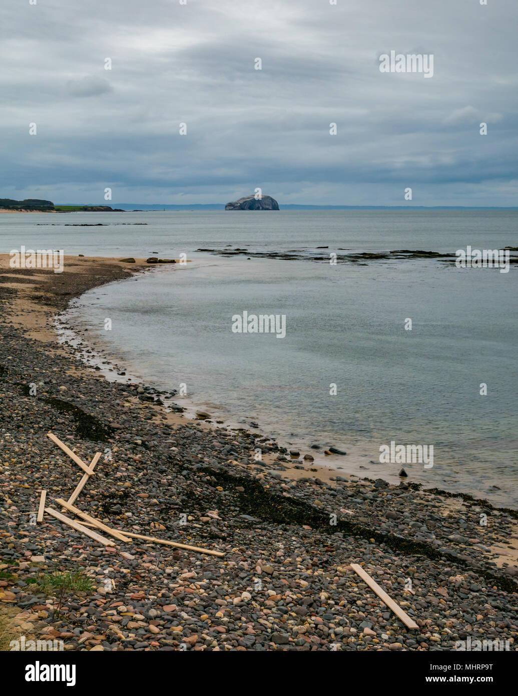 Ravensheugh Sands, East Lothian, Scotland, United Kingdom, May 2nd 2018. No-one on the beach looking across the Firth of Forth towards the Bass Rock, home to the world's largest Northern gannet colony. Planks of timber still lie washed up after spilling from cargo vessel 'Frisian Lady' which lost the timber bundles during severe weather on 2nd March during the 'Beast from the East' - Stock Image