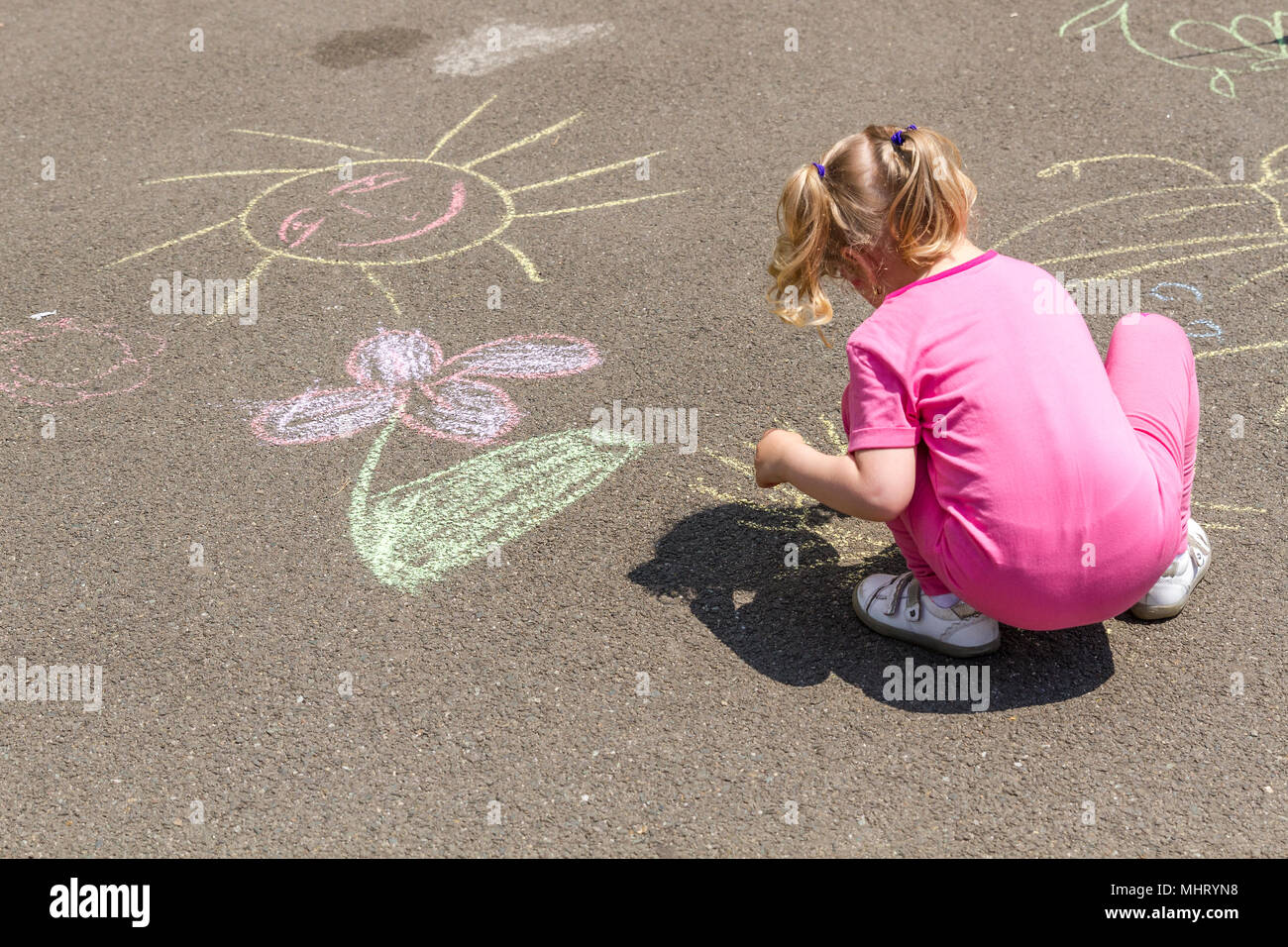 Young blonde girl in pink cloth drawing with chalk on asphalt. Image taken in a park, in a sunny day of summer. - Stock Image