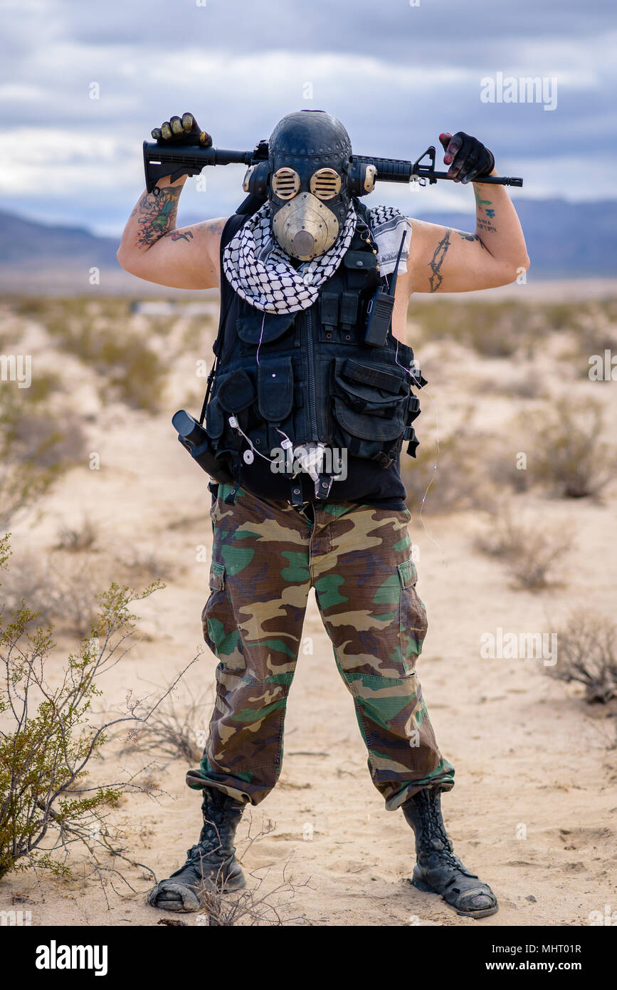 In a post-apocalyptic desert wasteland, a Queen of the Apocalypse leads her militia against the enemy. Armed to the teeth, who will win? Stock Photo