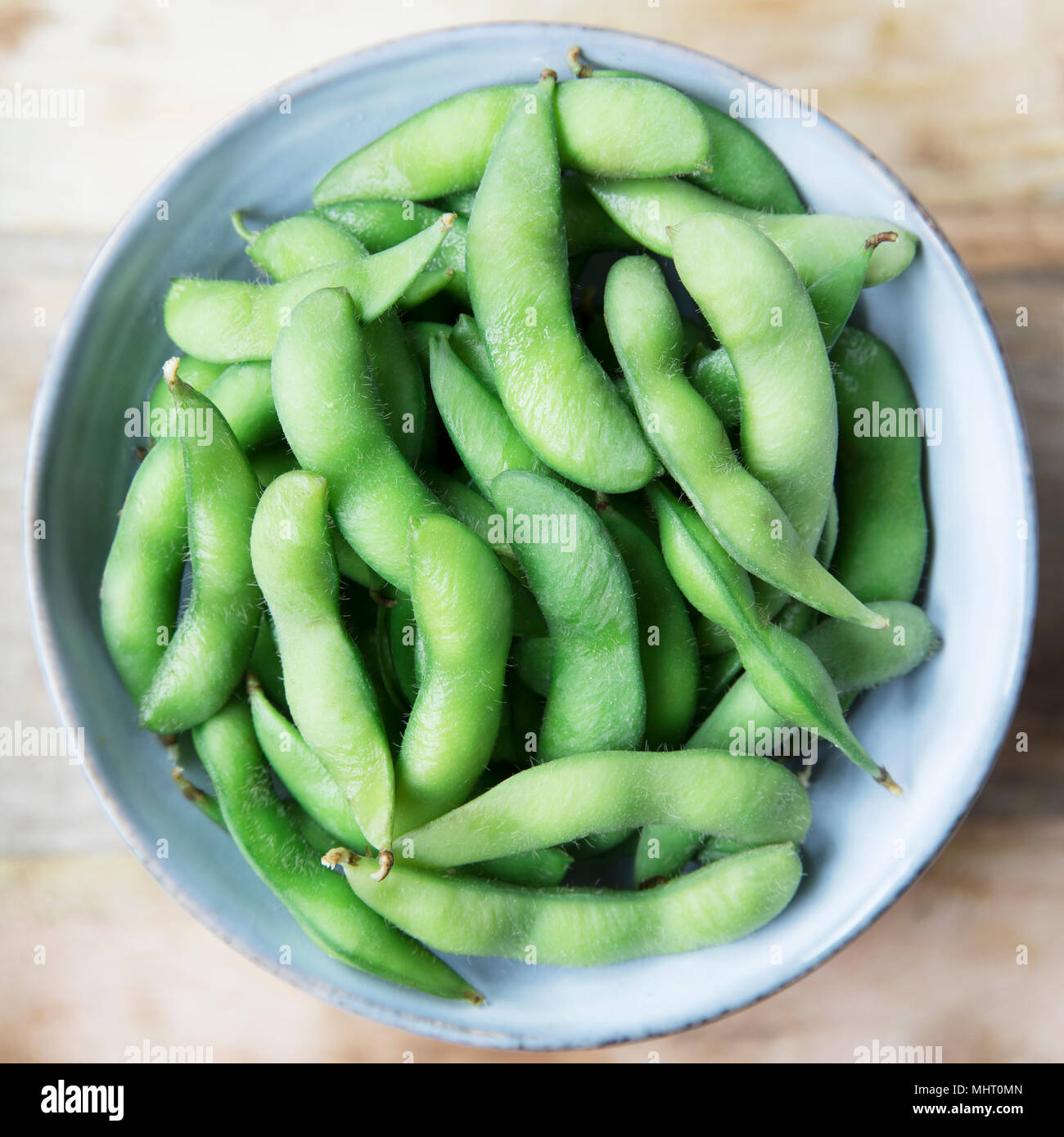 Fresh edamame in blue bowl from above. - Stock Image