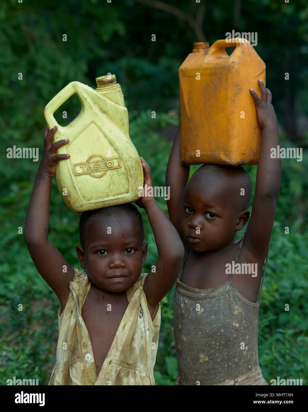 Children displaced by conflict carry water in a camp for internally displaced persons that formed around the Catholic church in Riimenze, South Sudan. - Stock Image