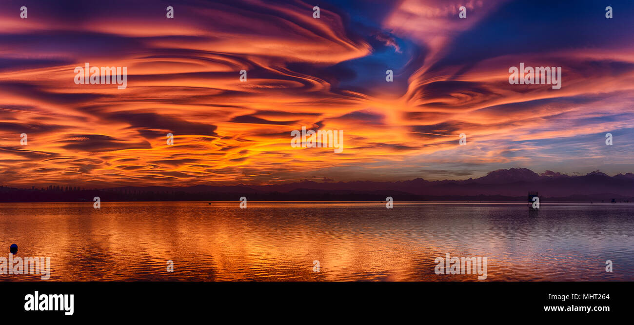 Incredible lenticular clouds in the sky during a sunset over the Varese lake - Stock Image