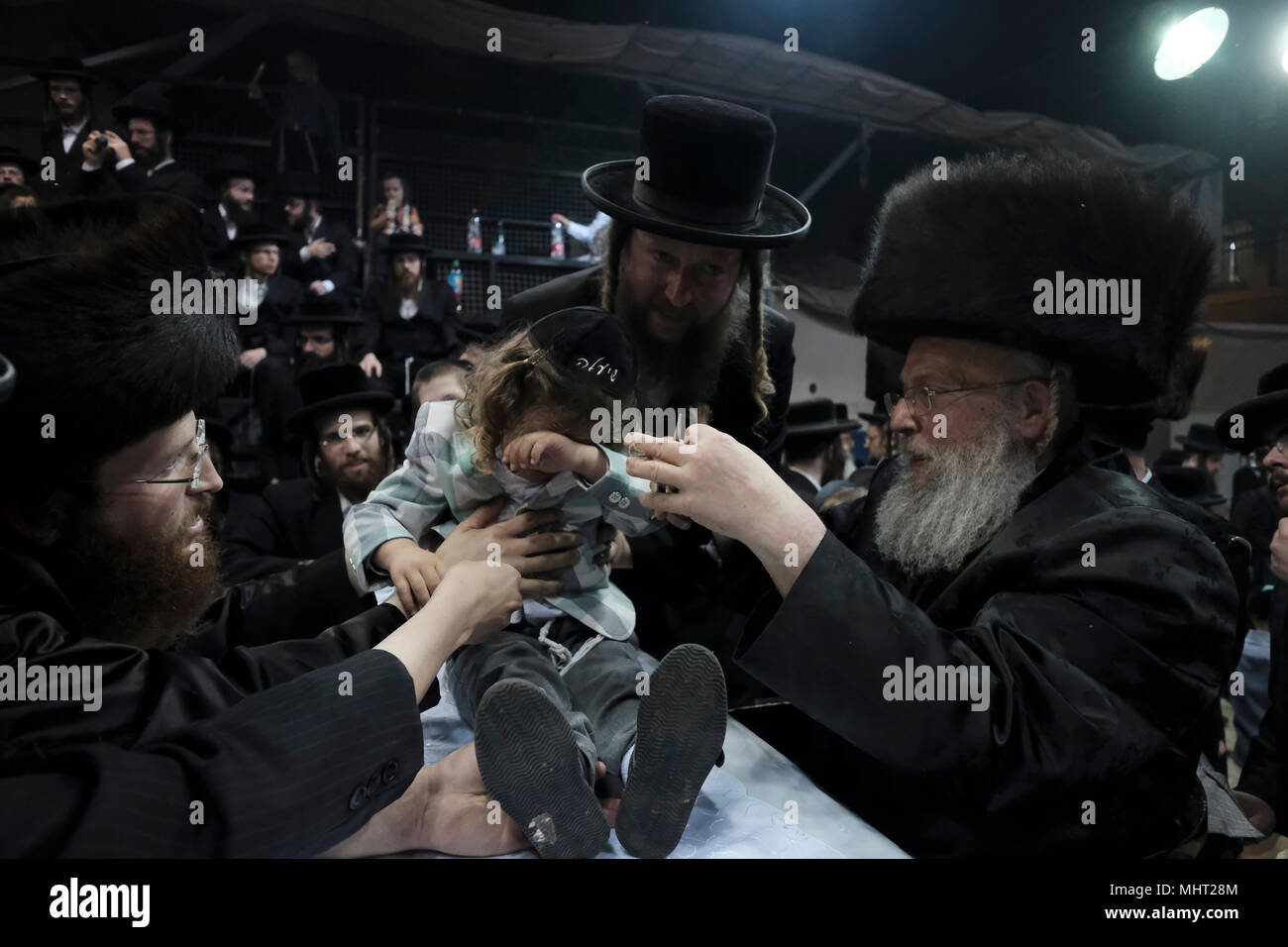 A three-year old Jewish boy takes part in the traditional Halake ceremony, a first hair cut from the Rabbi of the Pinsk-Karlin Hassidic dynasty in Geula religious neighborhood during the celebration of Lag BaOmer holiday which marks the celebration, interpreted by some as anniversary of death of Rabbi Shimon bar Yochai, one of Judaism's great sages some 1800 years ago and the day on which he revealed the deepest secrets of kabbalah a landmark text of Jewish mysticism - Stock Image