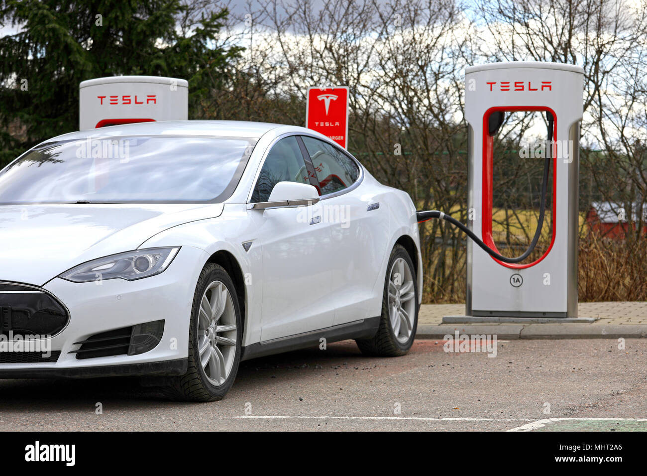 White Tesla Model S electric car connected and charging at Supercharger station on a day of spring in Paimio, Finland - April 28, 2018. - Stock Image