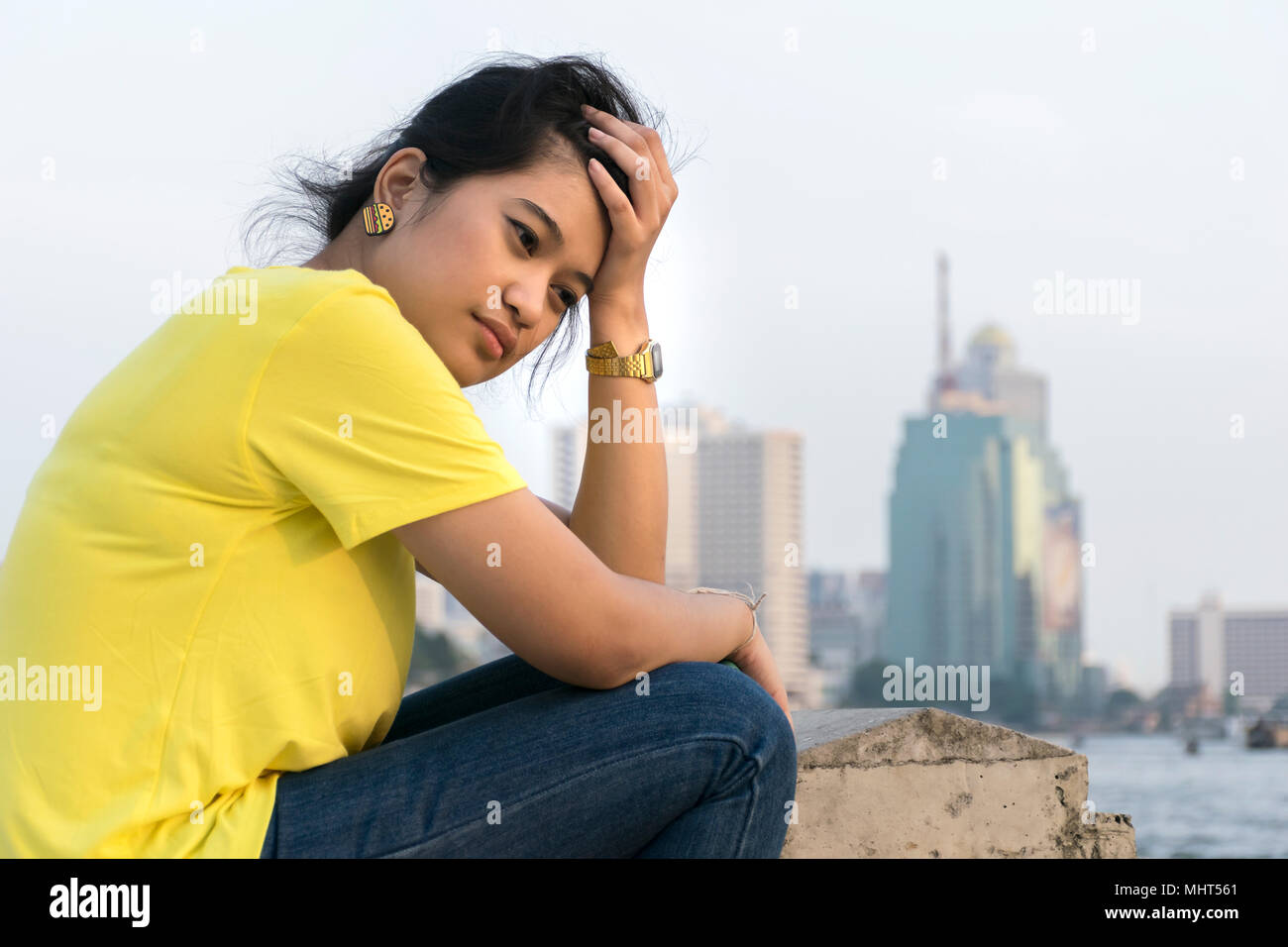 Asian women are feeling very strain,Wearing a yellow shirt,jeans,The hand is holding the hair on the head,Sitting on the river. Stock Photo