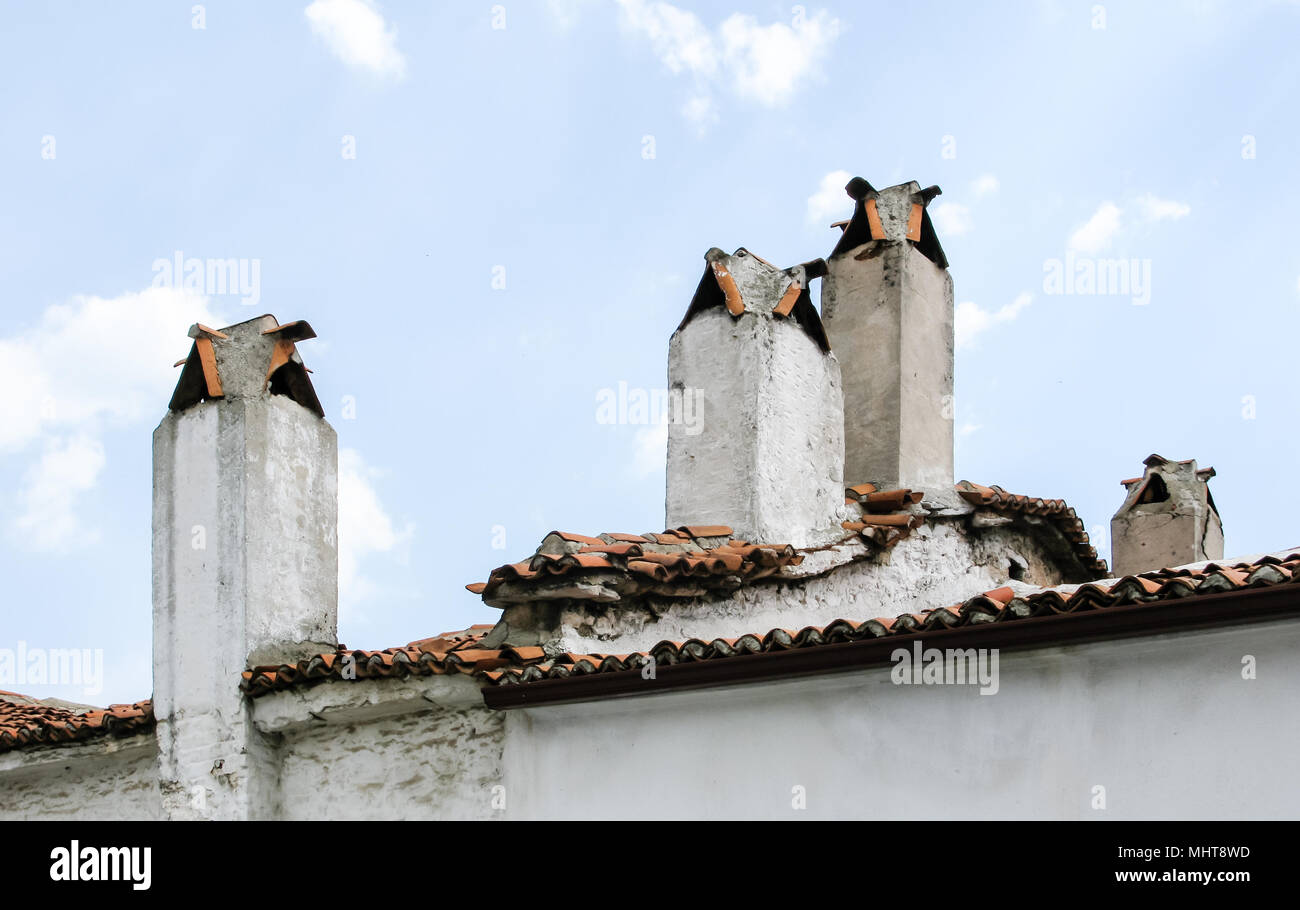 Old brick chimney on the roof. Air pollution. - Stock Image