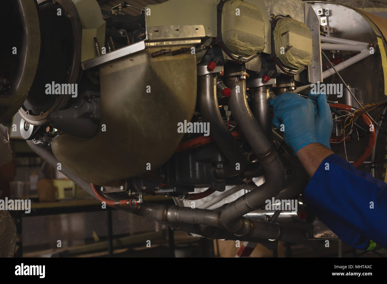 Engineer repairing aircraft engine in hangar - Stock Image