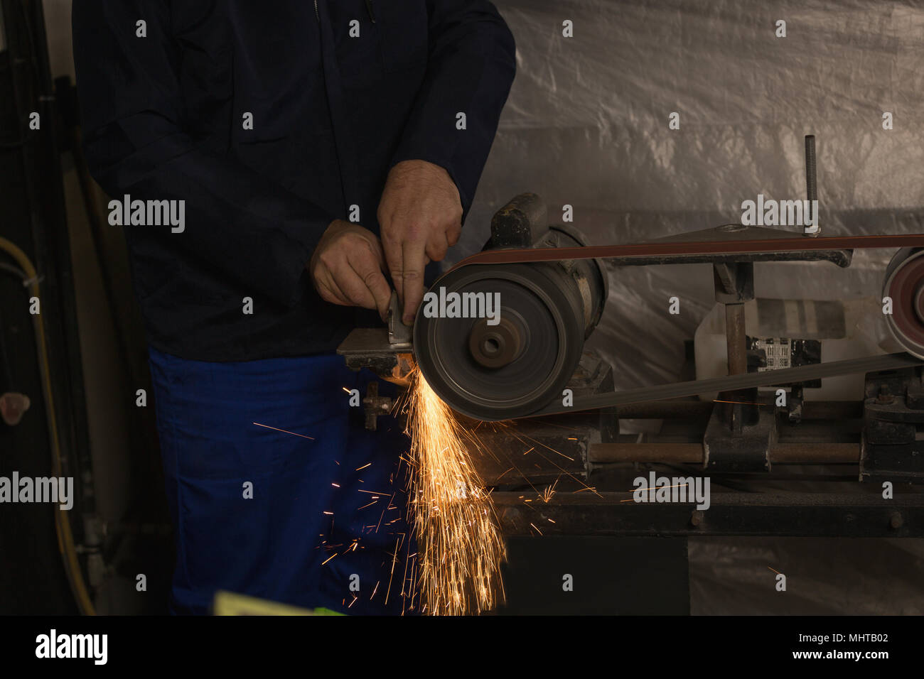 Worker shaping metal on machine - Stock Image